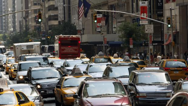 Cars, taxis and trucks sit in traffic in