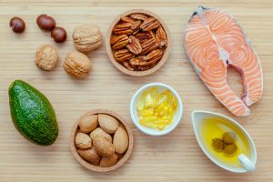 59039288 - selection food sources of omega 3 and unsaturated fats. super food high omega 3 and unsaturated fats for healthy food. almond ,pecan ,hazelnuts,walnuts ,olive oil ,fish oil ,salmon and avocado on wooden background .
