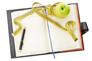20902585 - notebook and pen with apple and measuring tape for writing the diet notes